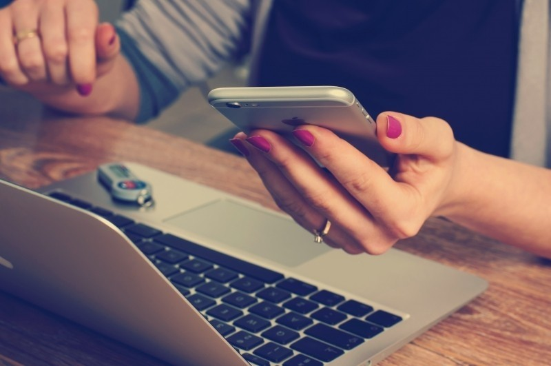 woman-text-messaging-with-laptop-on-wooden-table-1.jpg